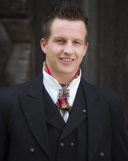 Mann med sort rundtrøyebunad med hvit skjorte